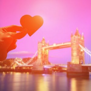 silhouette of romantic lovers hand hold love heart paper in Tower Bridge with sunset